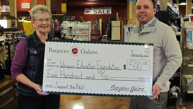Alice Posthuma, member of Bargains Galore committee, presents a $500 check to Derek L. Drews, Treasurer of Waupun Educational Foundation.