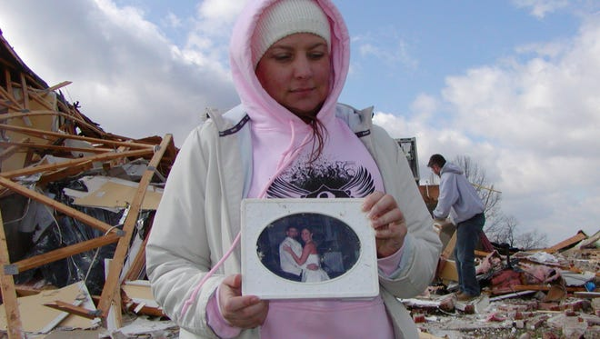 Tina Imhoff, whose house in Piner was destroyed by the March 2, 2012, tornado, holds a wedding photo a friend found during cleanup the morning of Saturday, March 3.