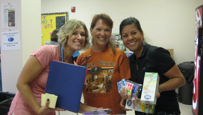 White Mountain Elementary school teachers Brooke Chavez, Cecilia Sanchez, and Aisela Magana.display some of the school supplies they chose from a trove donated by local staff members of PNM.