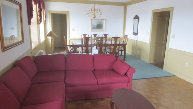 One of the elegant corner suites features living and dining areas with parquet wood floors and crown moldings.