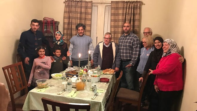 A family of Syrian refugees (two sons, daughter, mother and father on left) is welcomed by volunteers to a fully furnished apartment in Boonton provided for them by a faith-based coalition.