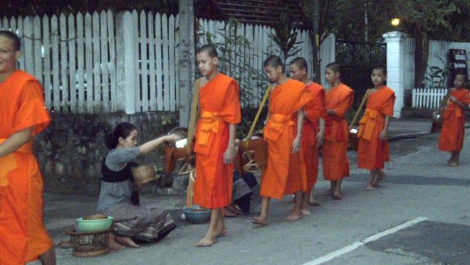 Orange-robed Buddhist monks receive alms from townsfolk in exchange for good karma.