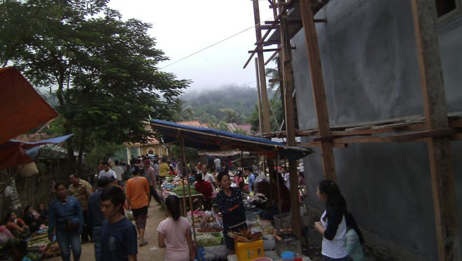 Early morning sees crowds of locals buying and selling at the outdoor market of Nong Khiaw in colorful Laos.