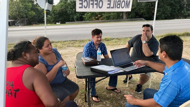 Sen. Wil Castro, right, meets with constituents at his mobile office in Dededo on Jan. 4, 2017.