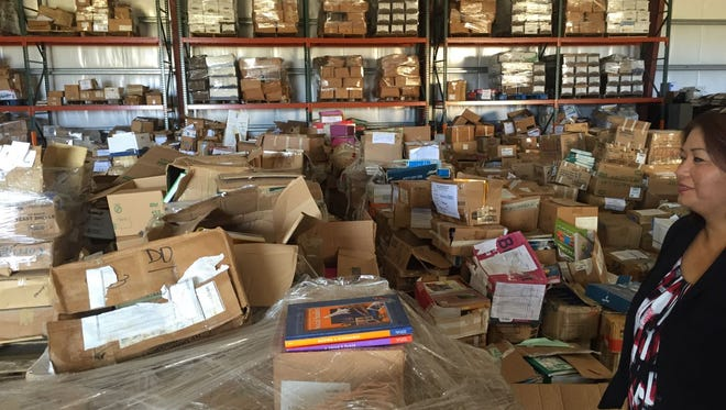 In this file photo, Michelle M. Camacho, textbook coordinator for the Guam Department of Education, shows old, outdated and damaged textbooks in a Tiyan warehouse.