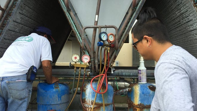 In this file photo, JRN Air Conditioning & Refrigeration technicians Rick De Leon, left, and Bernard Hilario, right, work on a Southern High School chilled water unit on March 24.