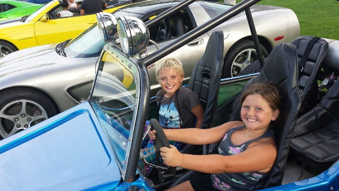 Jeremiah Roach, then 10, and Sarah Vanhevel, then 7, sit in a sand rail at Woodrow Wilson Elementary's open house. Tires and Treads donated shoes in muscle cars at the event.