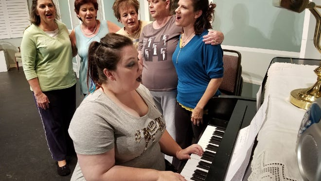 """Lynne Wagner, as Cora, plays the piano during a rehersal scene for Fremont Community Theatre's """"Calendar Girls."""" Pictured left to right is the rest of the cast, Darla Brown as Annie, Ann Stendera as Jessie, Beth Schweitzer as Chris, Karen Langley, as Karen and Melissa Karr as Celia."""