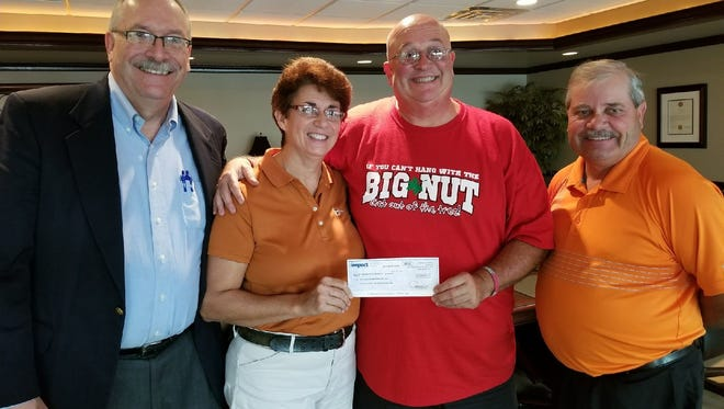 """A check in the amount of $51,000 is donated by Jon """"Big Nut"""" Peters and wife Terese Peters to the Ohio state University in October to be used for scholarship money for in-state students with a GPA of 3.5. Also pictured are Peter's attorney Jim Ellis,at left, and Louis Damschroder, right, the treasurer of Ottawa County Ohio State Alumni Association."""