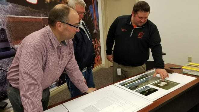 Gibsonburg Village Administrator Marc Glotzbecker, left, with councilman Don Kirwen, middle, and mayor Steve Fought, right, look at proposed plans for a medical marijuana cultivation facility approved by the Ohio Department of Commerce to be built in Clearview Industrial Park.