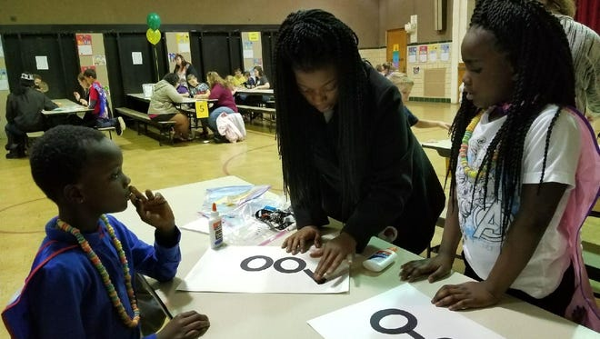 Chareese Harris with twins Kadyn, left, and Kamira Jones, work on a project during the 100 days celebration at Hayes Elementary.