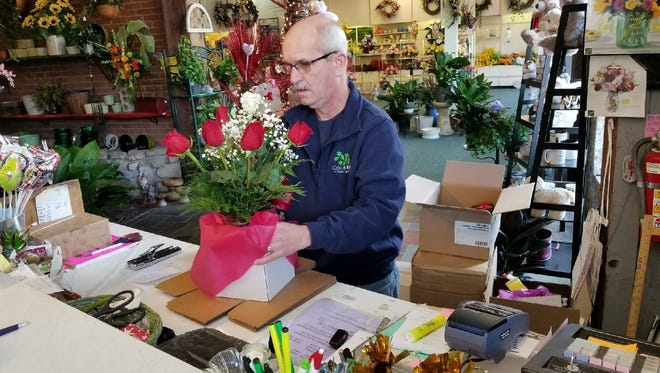 Hundreds of bouquets of flowers are sold each Valentine's Day at Otto Urban in Fremont. Designer Rick Heimbaugh prepares an order Wednesday.