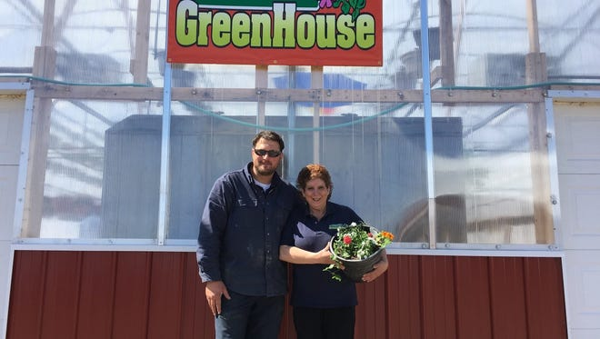 Owners Dusty and Brenda Schlinsog pose outside the recently constructed garden center at Turn Pike Greenhouse.