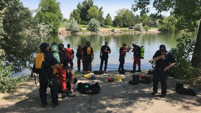 Divers prepare to search for a teenager they were told went underwater in Loveland Lake Monday afternoon. The 17-year-old later died from his injuries sustained from drowning.