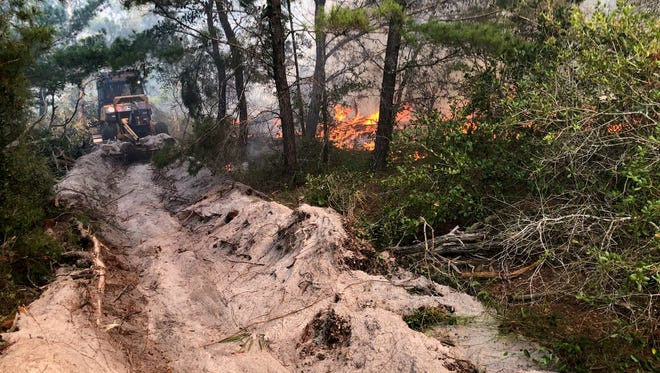 Firefighters use bulldozers Tuesday afternoon to battle two wildfires in Fort Pierce,