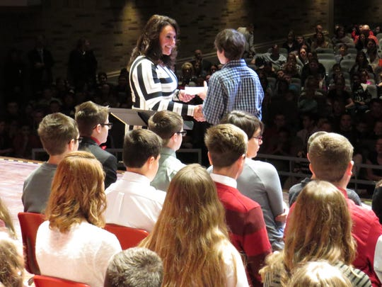 Port Clinton Middle School Principal Carrie Sanchez presents Jacob Weldon with his National Junior Honor Society certificate.