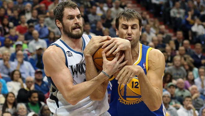 Minnesota Timberwolves power forward Kevin Love (42) fights for the ball with Golden State Warriors center Andrew Bogut (12) in the second half at Target Center.