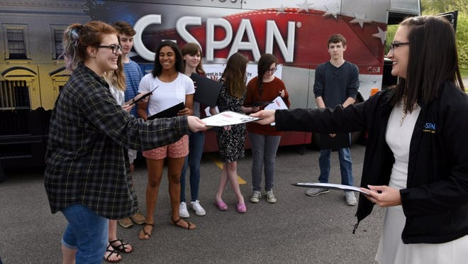 C-SPAN representive Chellie Zou, right, hands out awards to Leora Boyd, left, and other Hardin Valley Academy StudentCam winners in front of the C-SPAN bus Wednesday, April 20, 2016. (MICHAEL PATRICK/NEWS SENTINEL)