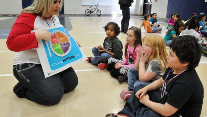 In this file photo, Candace Pichoff, left, teaches Sam Houston Elementary second graders Jhon Reynolds, left, Carly Davis, Gabrielle Moreland and Armando Rodriguez about healthy food choice during Healthy Kids Day, sponsored by Kids Kitchen, a Junior League of Wichita Falls community project. Obesity rates for children ages 2 to 4 who participate in WIC have dropped nearly two percent from 2010-2016.