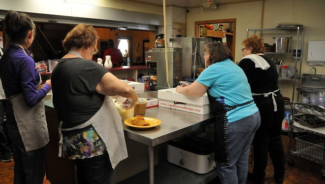 Volunteers help plate food for a free meal at Pontifex on Saturday.