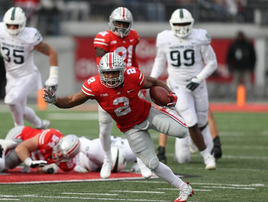 Ohio State's J.K. Dobbins runs by Michigan State defenders