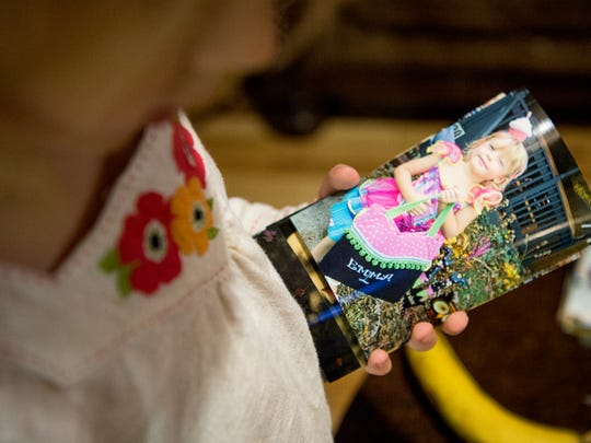 Emma looks at a photograph of herself dressed as a cupcake princess for Halloween. By the age of 3 Emma began showing signs that she is transgender.