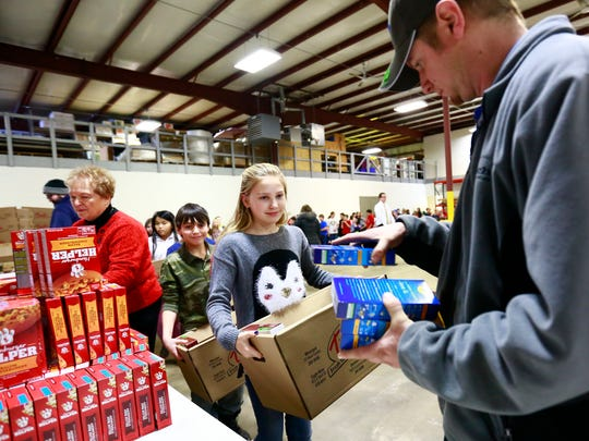 Fifth-grader Marisol Swenson, middle, waits in line with other students to fill up her cardboard box with food from employee Scott Jensen Friday afternoon at K-tech in Weston. Evergreen Elementary school's fifth grade students volunteer to package food in box to deliver to family in need this Sunday.