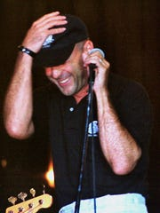 Actor and singer Bruce Willis gestures while singing