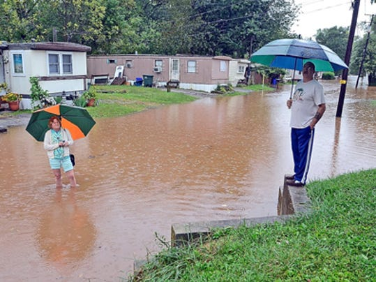 Chrissy Mannino, left, and her husband Tim nogotiate ankle-deep flood waters Tuesday down the street from their Dover Township home.