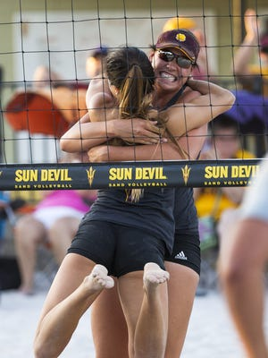 ASU's Whitney Follette (facing camera) and Bianca Arrellano celebrate after beating Arizona 2-1 in sand volleyball at Pera Club in Tempe April 20, 2016.