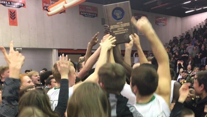 Oshkosh North players hold up the WIAA Division 1 boys basketball sectional plaque  as they are surrounded by their fans after a 57-42 win over SPASH on Saturday in Marshfield.