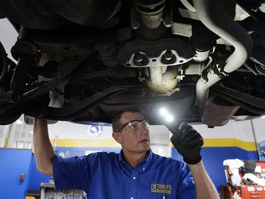 Service manager Chad Fadely uses a battery-powered light to check the exhaust system as he demonstrates a safety inspection on a Subaru on Friday, June 26, 2015, at Fadely's Auto Masters + Tires in West Manchester Township.