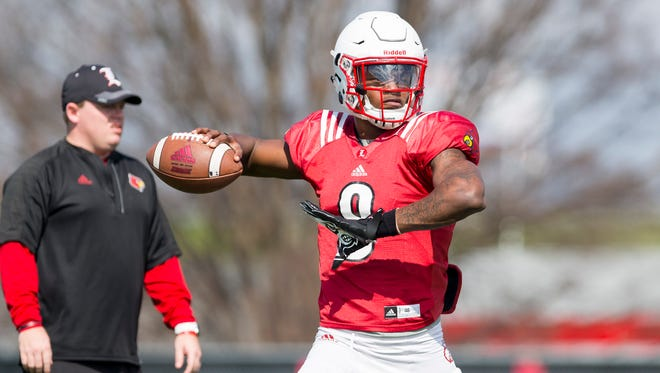 Louisville quarterback Lamar Jackson throws the ball during Louisville's spring football practice while QBs coach Nick Petrino looks on.