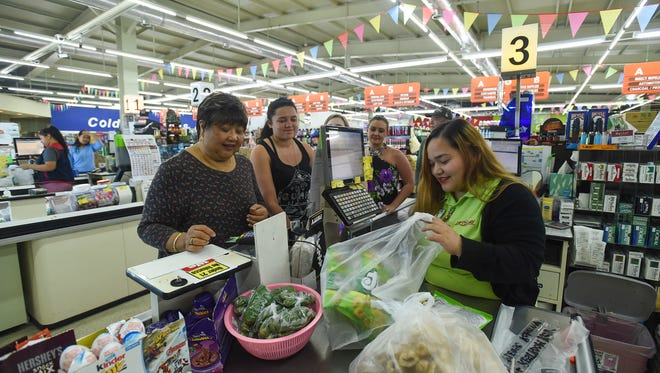 Day Buy Day supervisor Tasha Cabrera, right, bags chips for customer Edith Gallandez, left, during a transaction in Piti on Feb. 2, 2018.