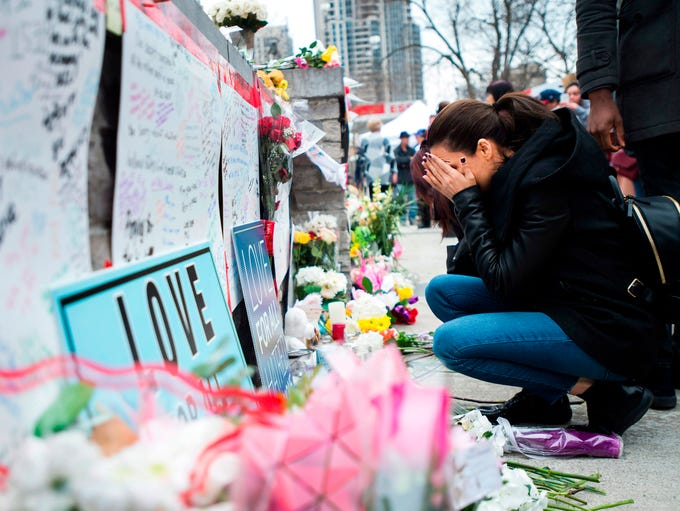 A women fights back tears at a memorial along Yonge