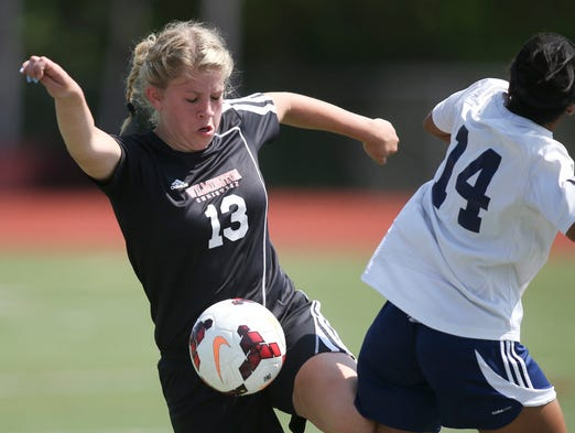 Wilmington Christian's Katelyn Stonkus (left) vies for the ball with Sanford's Amira Hannon as Sanford tops Wilmington Christian, 3-0, in the first round of the DIAA girls high school state tournament Saturday, May 17, 2014 at Caravel Academy.