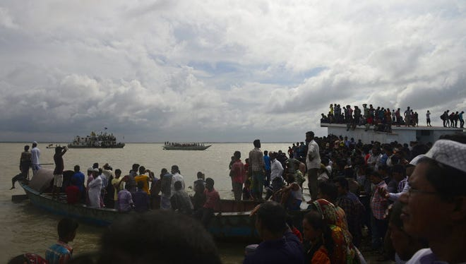 Bangladeshi onlookers gather near the scene where an overloaded ferry capsized in the Padma river in Munshiganj, about 20 miles south of the capital Dhaka, on Aug. 4.