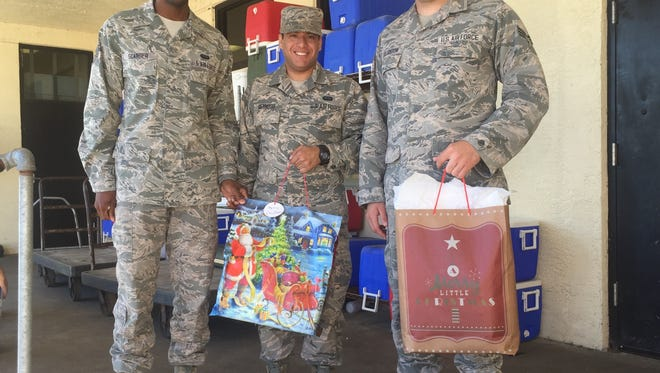 Staff Sergeant Frederick Scarber, left, and Senior Airmen Aldonys Reynoso and Nicholas Creighton, who deliver Meals on Wheels every Wednesday, dropped off Reaching Out Holiday Fund gifts with the meals on their Dec. 13 route. The men, stationed at Patrick Air Force Base, say volunteering has changed their lives and hopefully, the lives of those they meet.