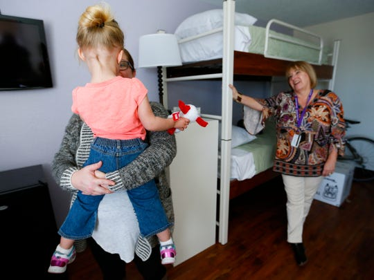 Esther Munch, Harmony House marketing director, holds the daughter of a resident of Harmony House as Lisa Farmer, Harmony House executive director, look on in a new resident room on Thursday, Feb. 16, 2017.