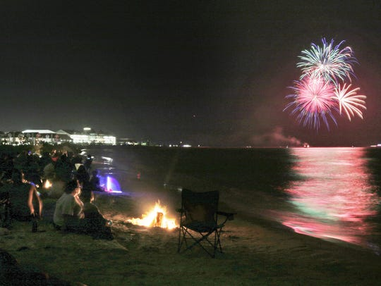 People sit by their fire pits as fireworks explode