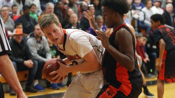 From left, Mamaroneck's Thomas Plunkett (32) tries to get around Spring Valley's Xavier Miles (10) during Section 1 boys basketball playoff action at Mamaroneck High School Feb. 23, 2018. Mamaroneck won the game 49-42.