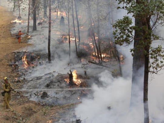 Firefighters hose down hot spots along the containment line on a controlled burn as they attempt to fight the King Fire in 2014.