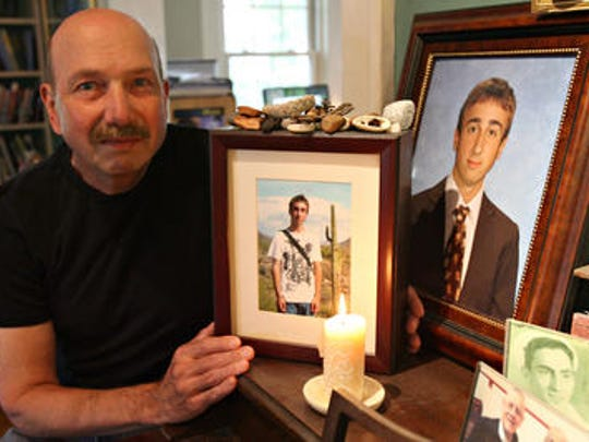 Jeffrey Veatch with photos of son Justin