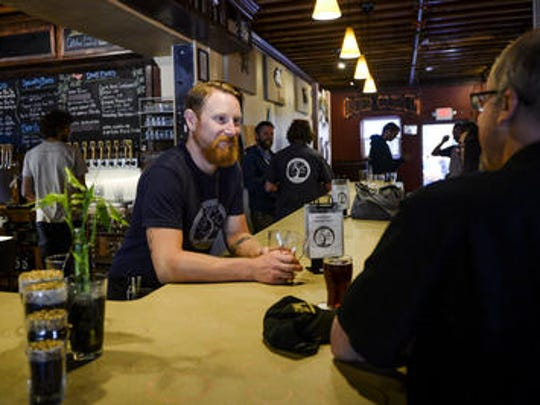 Nathan Kaczmarek helps costumers at Equinox Brewing.