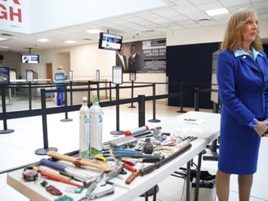 Sari Koshetz, a spokesperson for TSA, stands near a table of voluntarily abandoned property at Tallahassee International Airport on Wednesday. Items such as brass knuckles, knives and the empty shell of a grenade, though not illegal, are prohibited on checked luggage and are left behind by passengers to the tune of 4100 pounds of property at TLH this year. These items can also lead to heavy delays with security checkpoints at the airport.