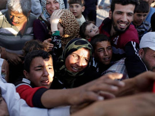 Syrian refugees wait for supplies near the Turkish