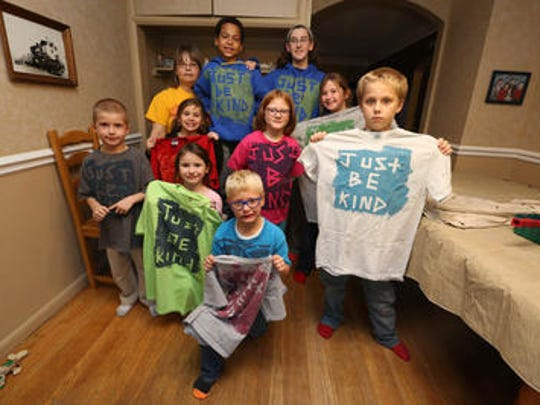 Members of the Just Be Kind Kids Club show off T-shirts they painted at Andrea Flood's house. Flood (orange shirt) is pictured with Damon Henderson, Sarah Stratton, Blayze Burnett, Hannah Smith, Avolyn Gonser, Emily Smith, Lilly Smith, Hunter Kiplinger and Elliott Gonser.