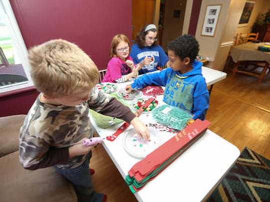 Hunter Kiplinger (left), Avolyn Gonser, Sarah Stratton and Damon Henderson decorate Just Be Kind holiday sticks to sell at a craft fair.