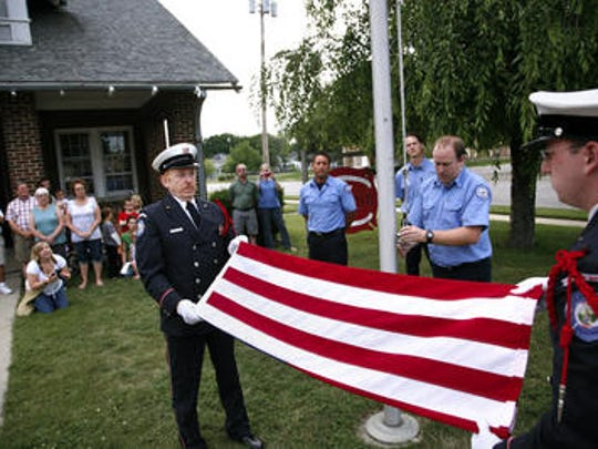 Stephenm Babcock (left) and Eric Haueter, members of the Lansoing Fire Department Honor Guard, in 201 retire the flag that flew in front of Station No. 7.