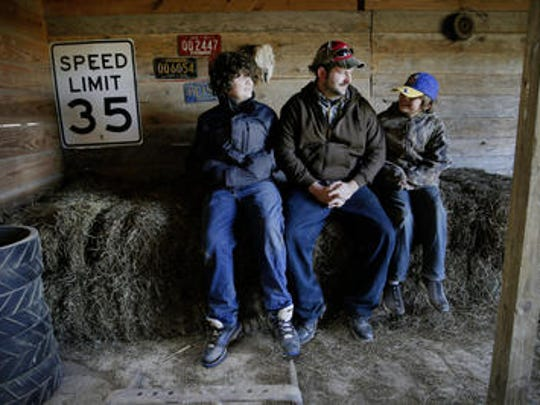 Jonathan Lawler and sons Elijah, 13, and Daniel, 10, take a break in the barn.